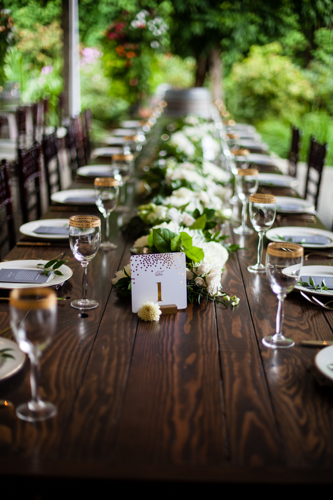 Barnwood Table rentals by Seattle Farm Tables -Photo by La Vie Photography, Venue - Delille Cellars in Woodinville, WA - Classic greenery with white florals. Gold rimmed glasses on dark wood. Wedding table scape - We rent wood tables in the Puget Sound area, Seattle, Tacoma, Woodinville, Eastside, San Juan Islands, Snohomish, Kitsap, Seatac Washington. Outdoor wedding, long table. Rustic tables, winery rentals, vineyard tables, fancy, classic design