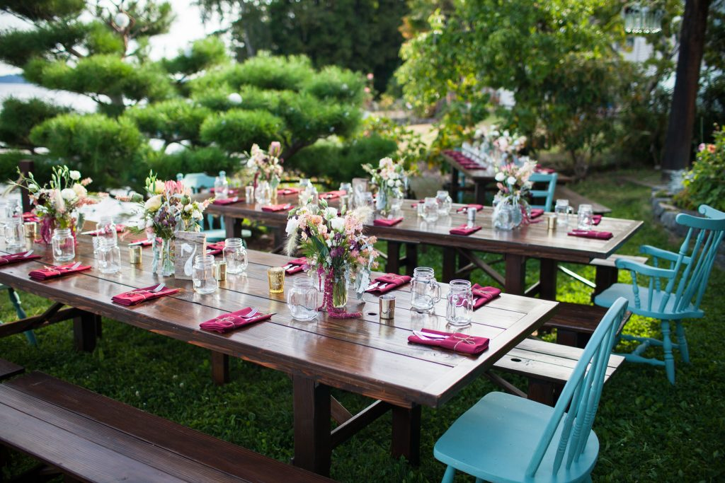 Thin Barnwood Table rentals by Seattle Farm Tables - Photo by Simonak Photography - Raspberry and teal accents with pastel flowers. Waterfront wedding on the Kitsap Penninsula. - We rent dark brown wood tables in the Puget Sound area, Seattle, Tacoma, Woodinville, Eastside, San Juan Islands, Snohomish, Kitsap, Seatac Washington. Outdoor wedding, long table. Rustic tables, winery rentals, vineyard rentals, wedding rentals, fancy, classy, classic design