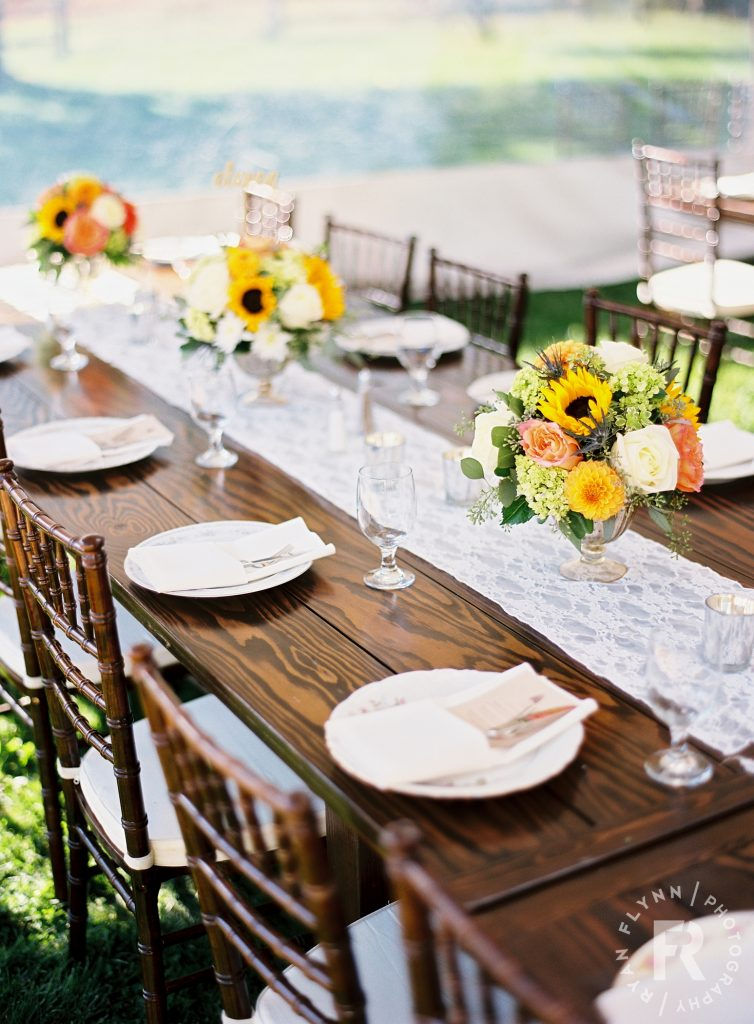 Barnwood Table rentals by Seattle Farm Tables -Photo by Ryan Flynn Photography, Planner - Pink Blossom Events, Flowers by Fawn Meadow Florals, Venue - Spring Creek Ranch in Winthrop, WA- Sunflowers and dark tables, coral and yellow centerpieces, lace runner, simple wedding arrangement. - We rent wood tables in the Puget Sound area, Seattle, Tacoma, Woodinville, Eastside, San Juan Islands, Snohomish, Kitsap, Seatac Washington. Outdoor wedding, long table. Rustic tables, winery rentals, vineyard rentals, wedding table rentals, classic design